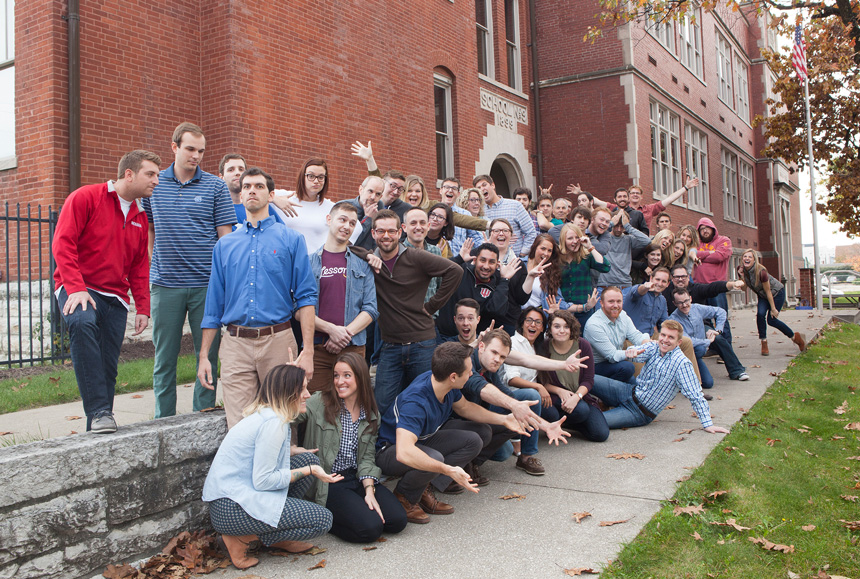 A large group of teammates posing in front of the Lessonly HQ.