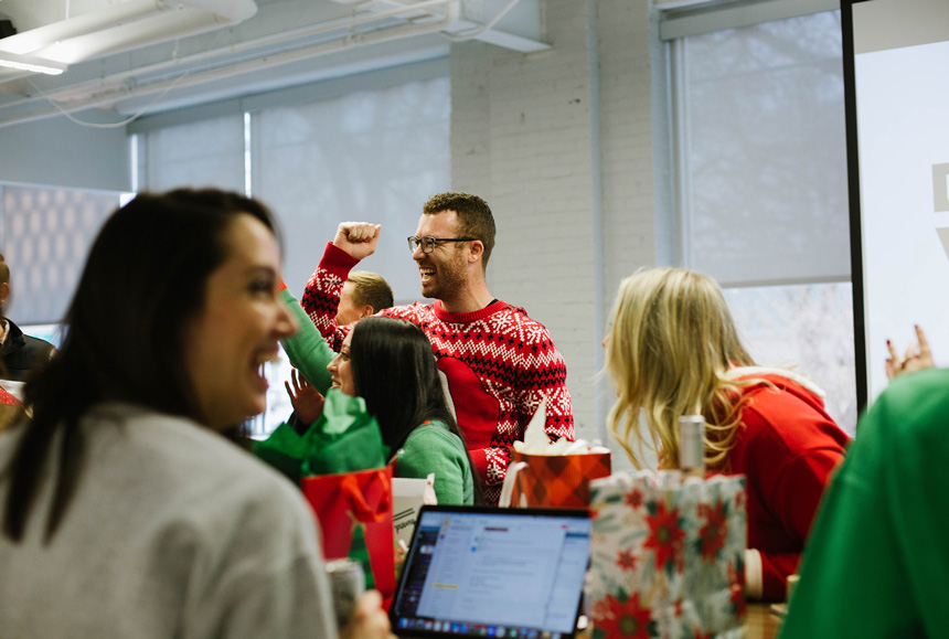 A man in a holiday themed sweater celebrating with a group of people.